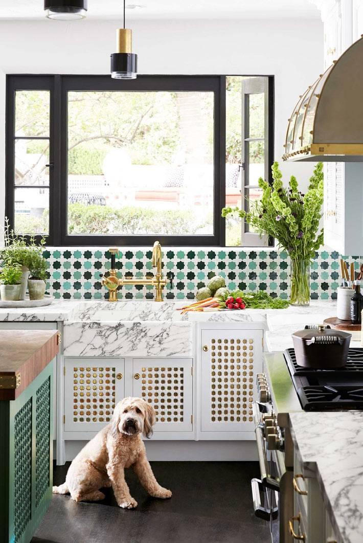 на большой кухне раковина с латунными кранами установлена под окном