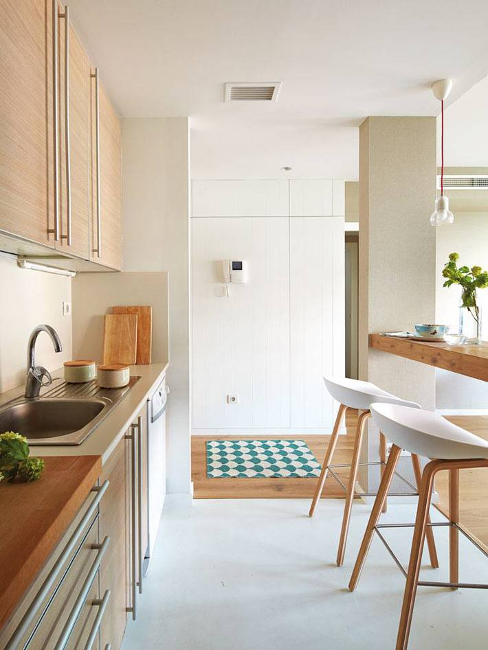 деревянная кухонная мебель и барная стойка с белыми пластиковыми стульями