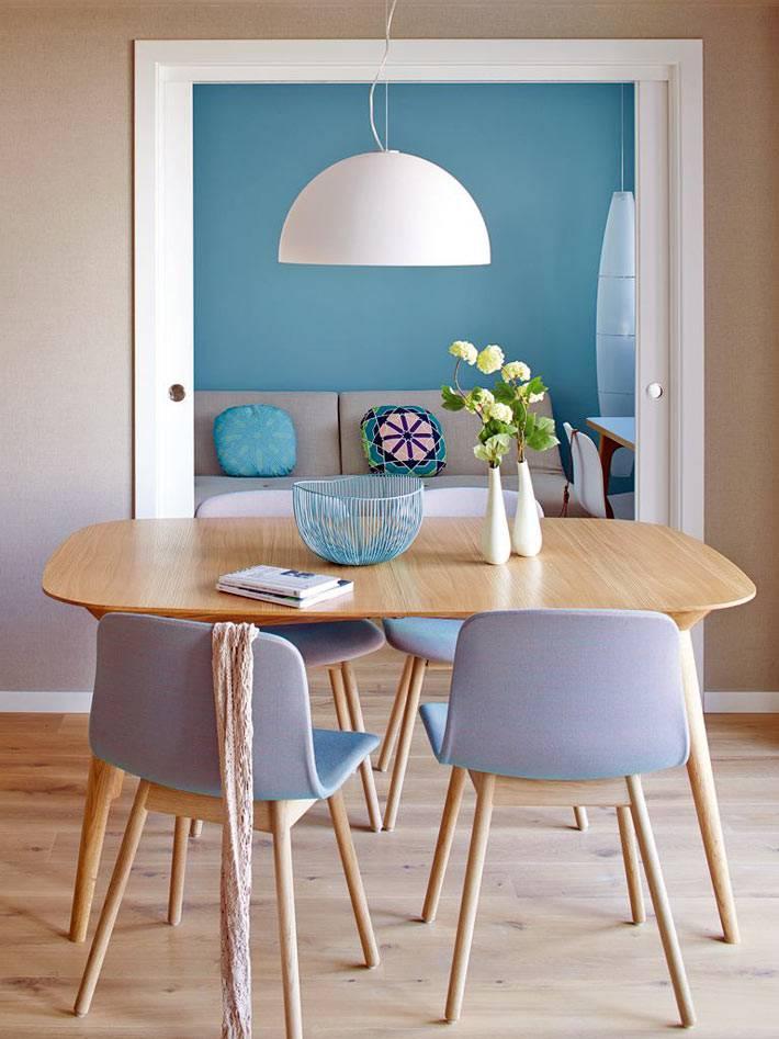 небольшой овальный обеденный стол из светлого дерева в квартире