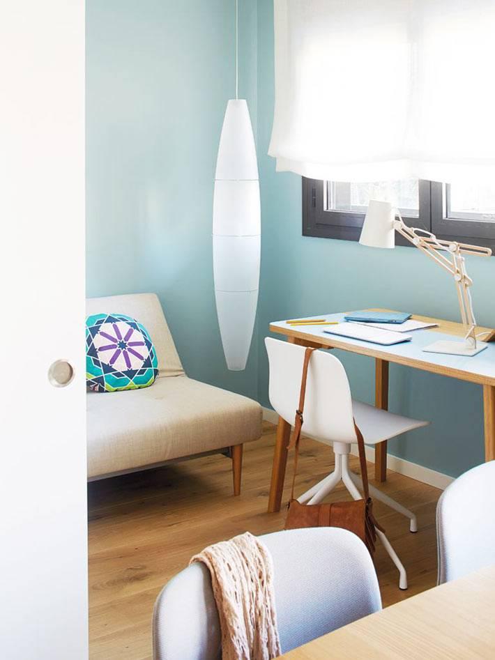 светло-голубые стены в комнате с диваном и рабочим столом возле окна