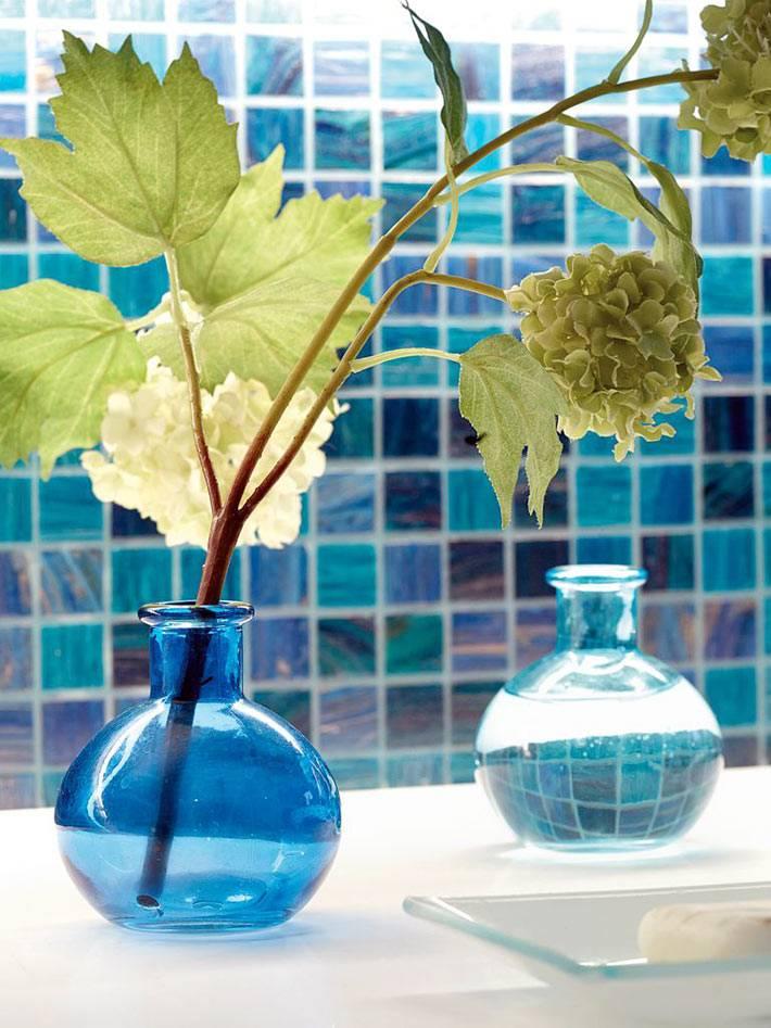 маленькие стеклянные вазочки синего цвета украшают пространство ванной комнаты