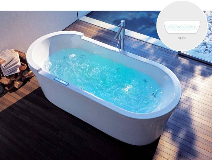 красивая отжельностоящая гидромассажная ванна на деревянном полу