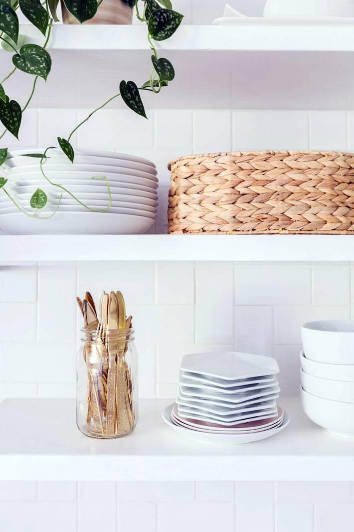 белые тарелки и плетеная корзина на открытых полках кухни