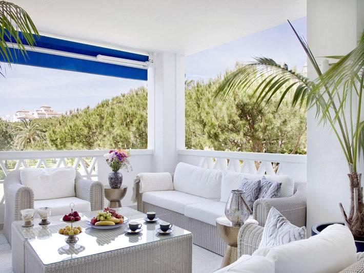 белая терраса с белой плетеной мебелью и видом на горы