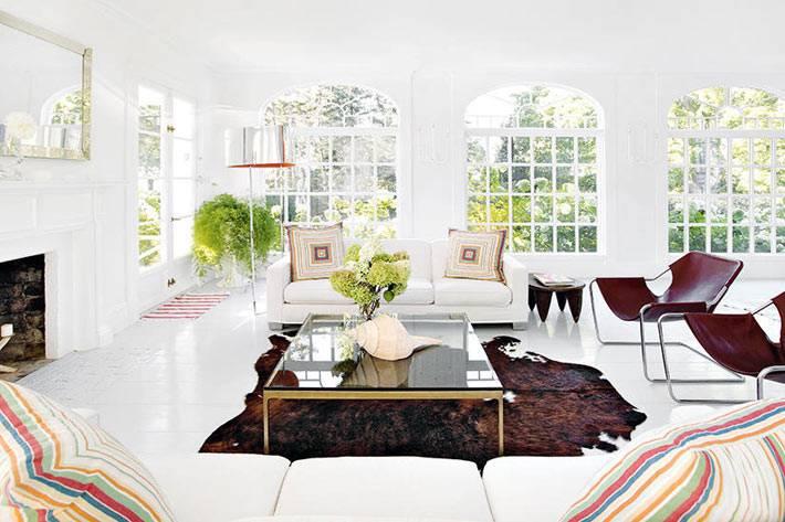 белые диваны и коричневые кожаные кресла в интерьере гостиной