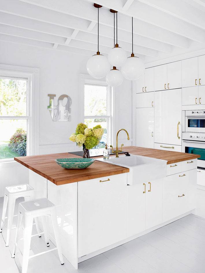 латунная фурнитура на кухонной мебели белого цвета фото
