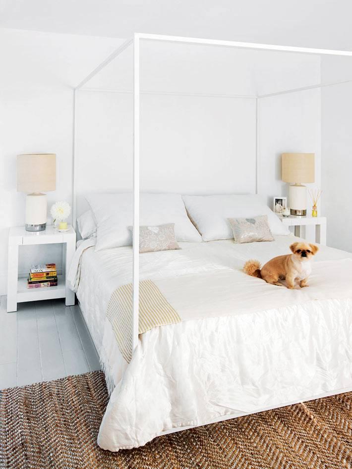 в белой спальне стоит кровать с рамой для балдахина