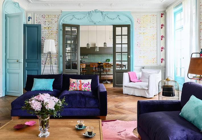 фиолетовые бархатные диваны в центре гостиной комнаты квартиры