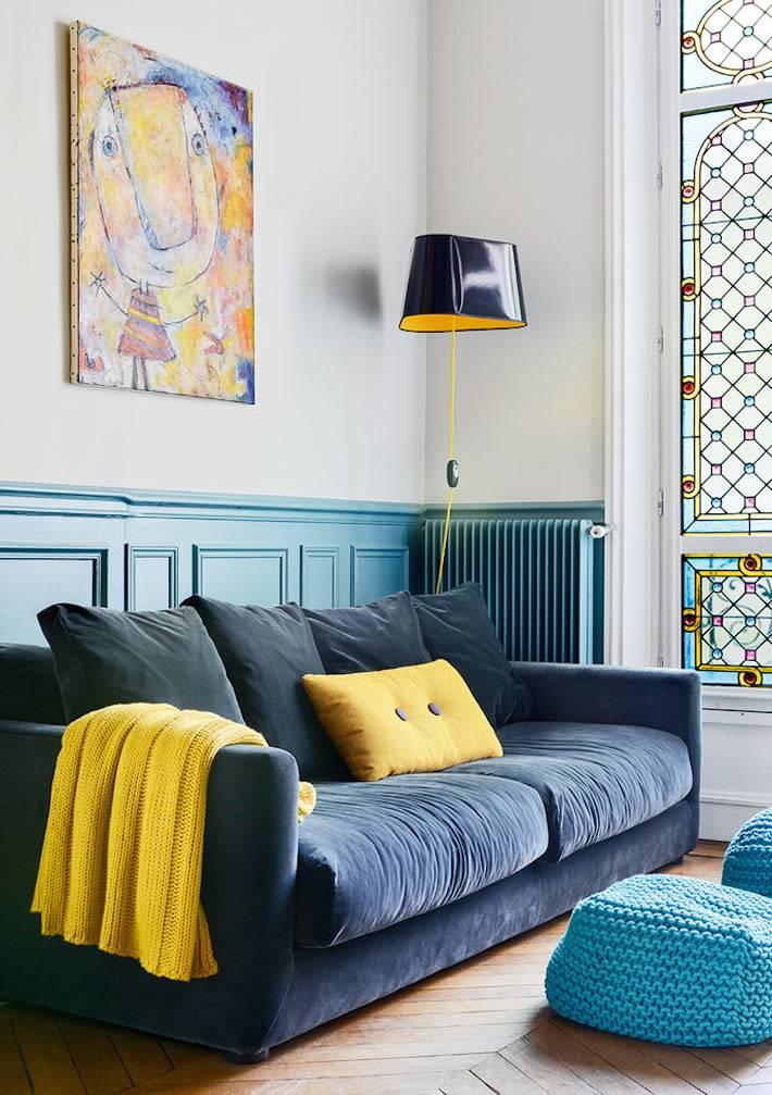 кврасивый темно-синий диван с яркими желтыми акцентами и торшер