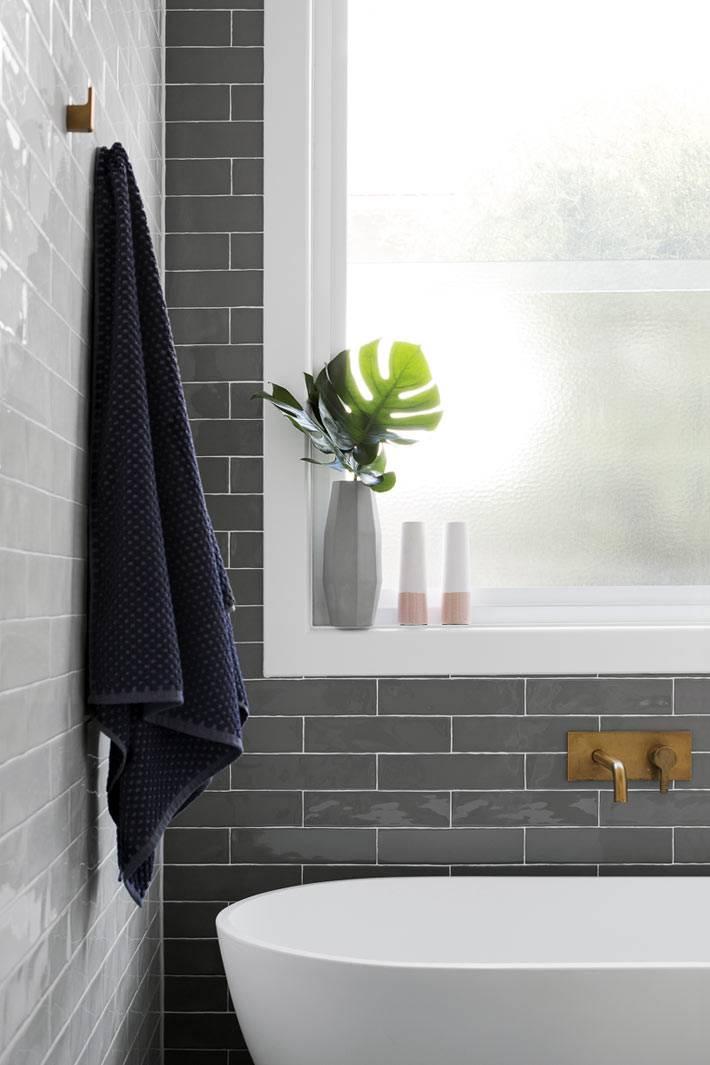белая ванна напротив серой акцентой стены в белом интерьере ванной комнаты