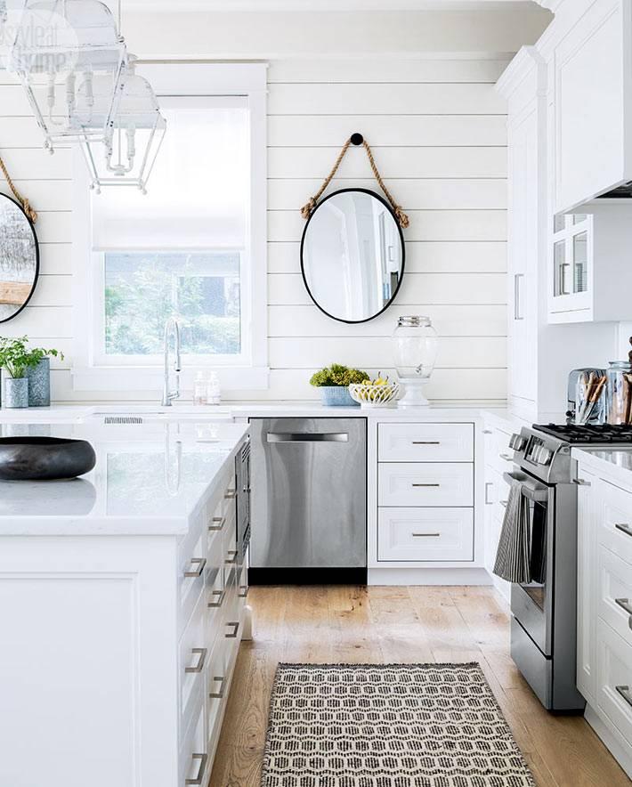 овальные зеркала на деревянной стене белой кухни