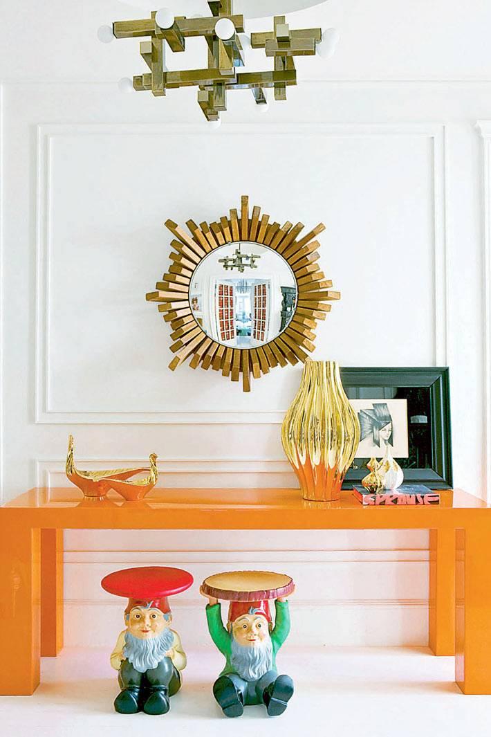 оранжевая консоль в доме и зеркало в раме формы солнца