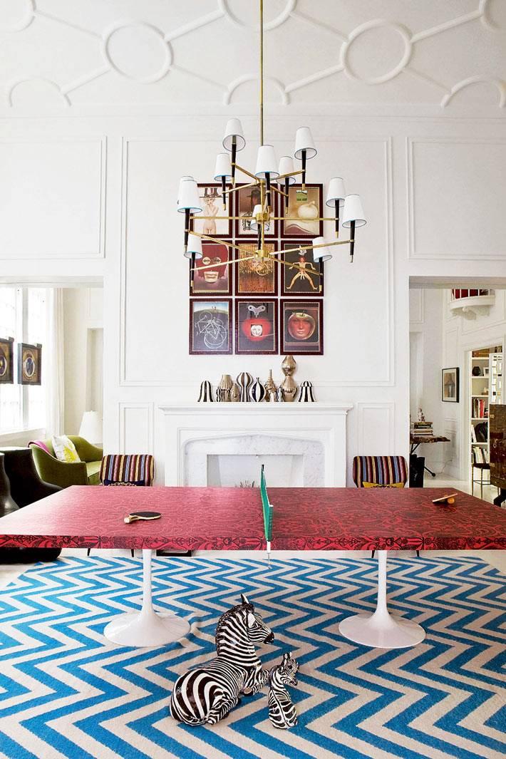 теннисный стол в центре гостиной с белыми стенами и пестрым синим ковром