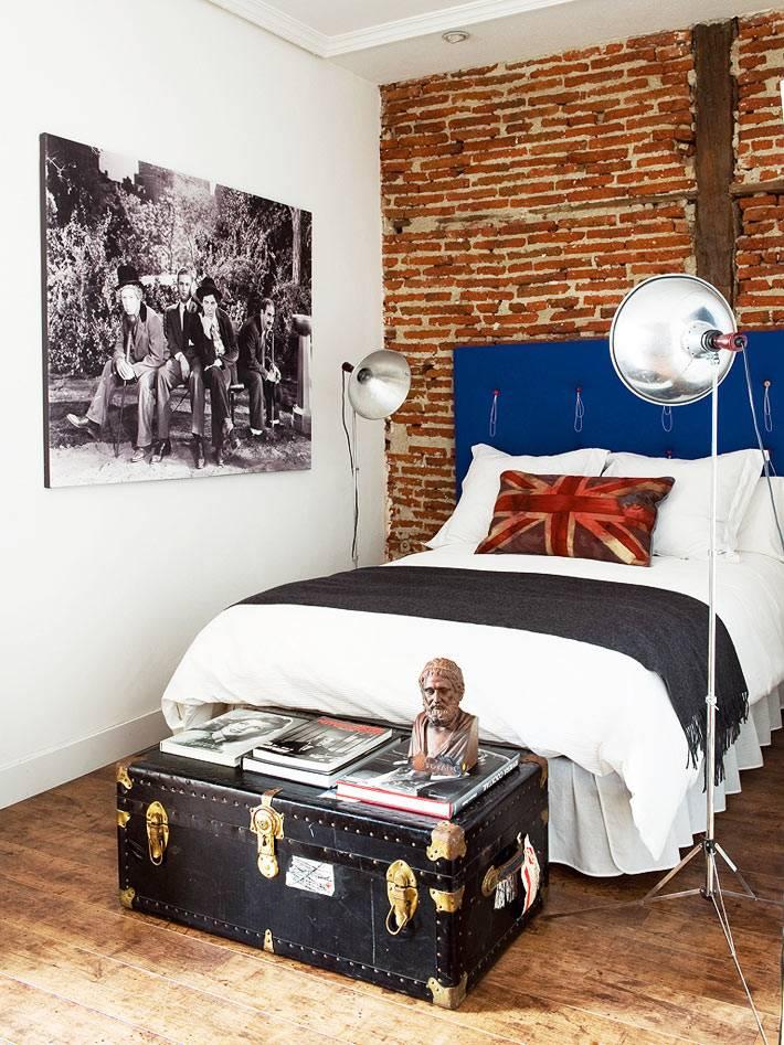 большой сундук и кирпичная кладка в интерьере спальни фото