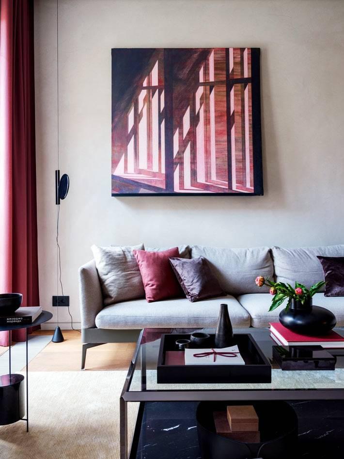 стены гостиной покрыты микроцементом и украшены картинами
