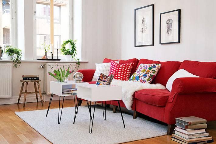 дизайн гостиной с красным диваном и белым столом