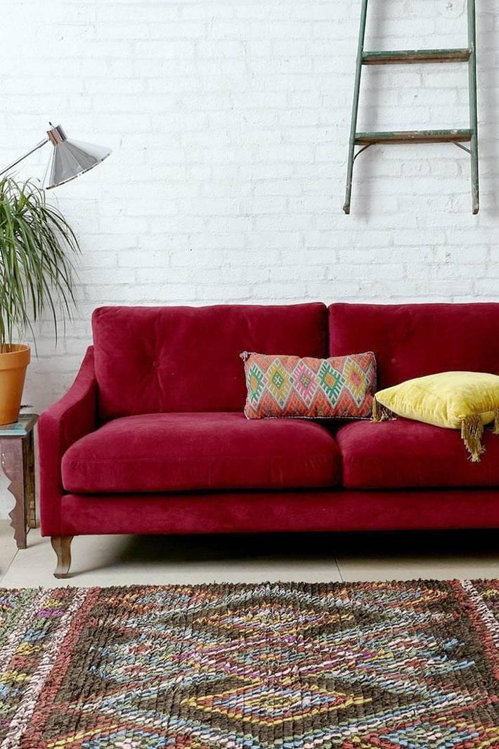 диван красного цвета вохле белой кирпичной стены в доме