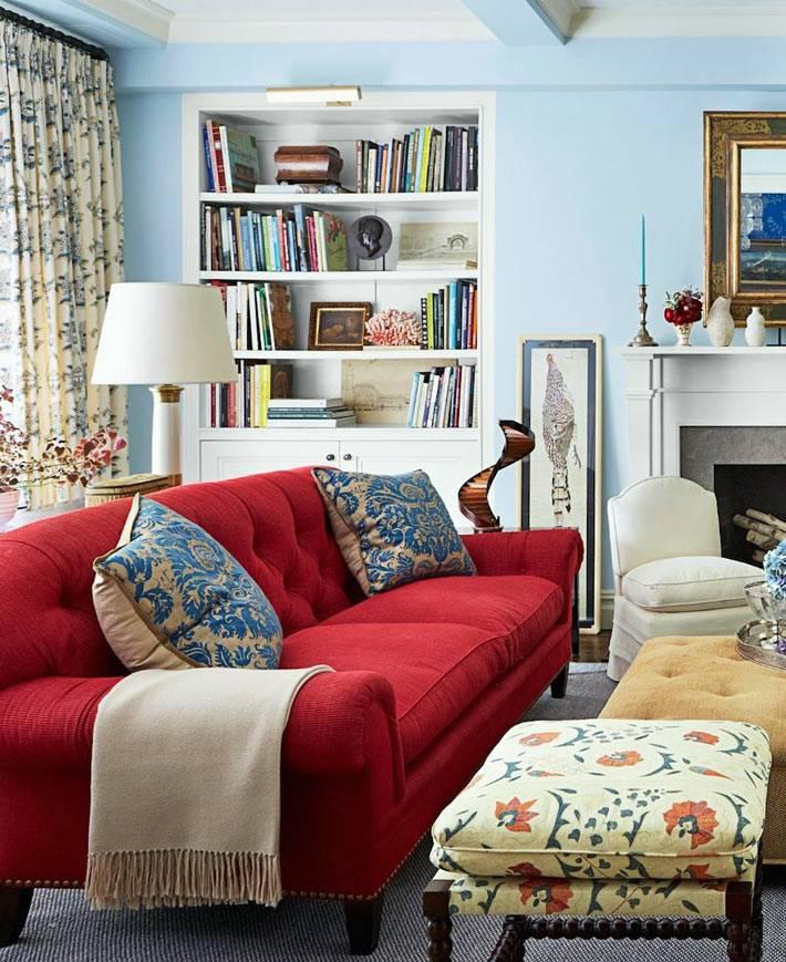 голубые стены комнаты с ярким красным диваном фото