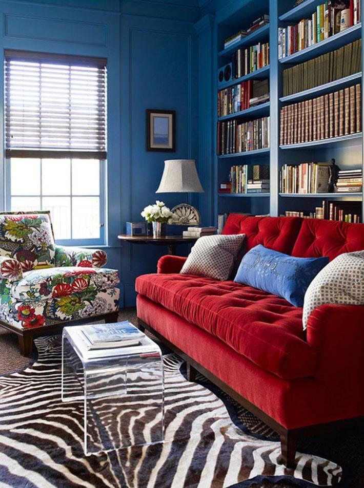 интерьер библиотеки с синими стенами и красным диваном