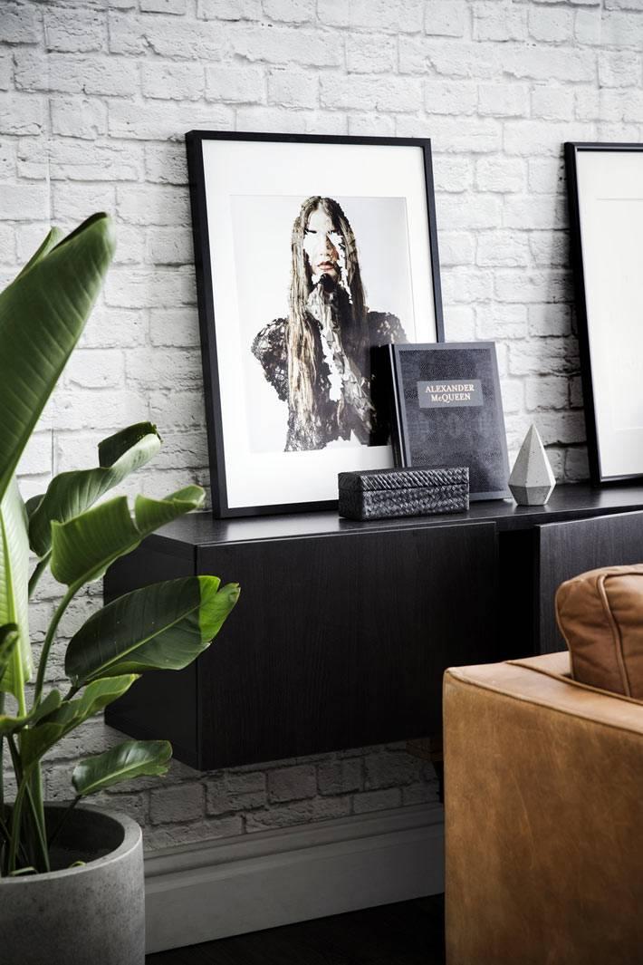 подвесная тумба черного цвета на белой кирпичной стене