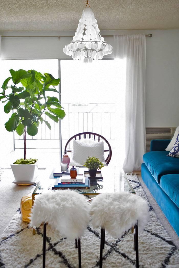 пушистый ковер и накидки на стулья белого цвета в гостиной