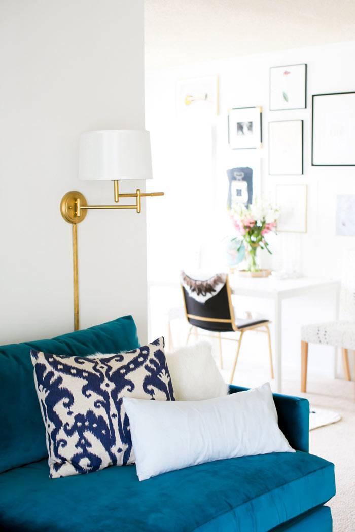 настенный бра с золотистой фурнитурой на белой стене