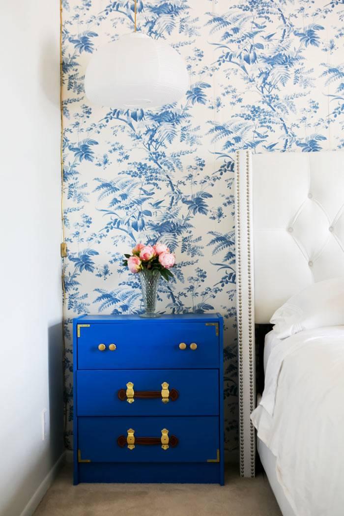 блая кровать с высоким подголовником возле стены с синими обоями