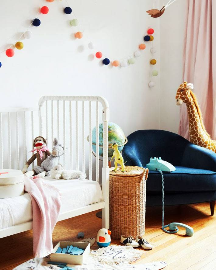 гирлянды из разноцветны хлопковых шариков в детской комнате
