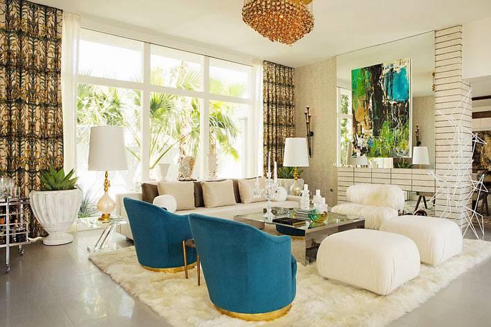 красивый интерьер гостиной с синими креслами и зеркальным столом в центре