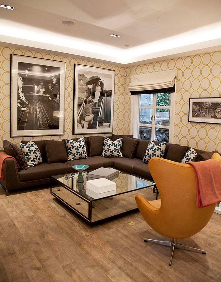 кино-постеры на стене в большой комнате с оранжевым креслом-яйцом