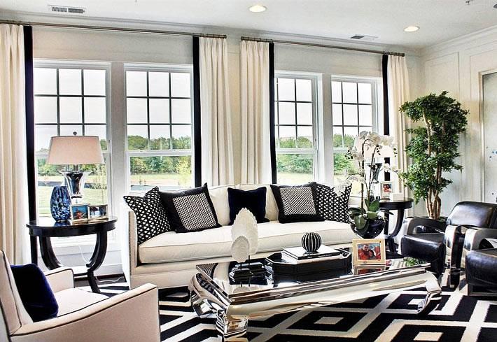 элегантный зеркальный журнальный стол в комнате с белым диваном