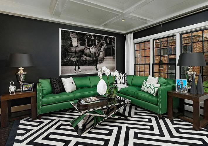 современный зеркальный столик в комнате с черными стенами и зеленым диваном