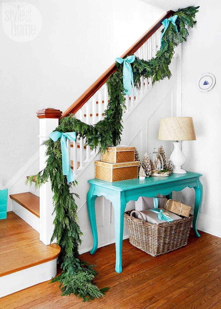 еловая гирлянда с голубыми бантами на перилах лестницы в доме