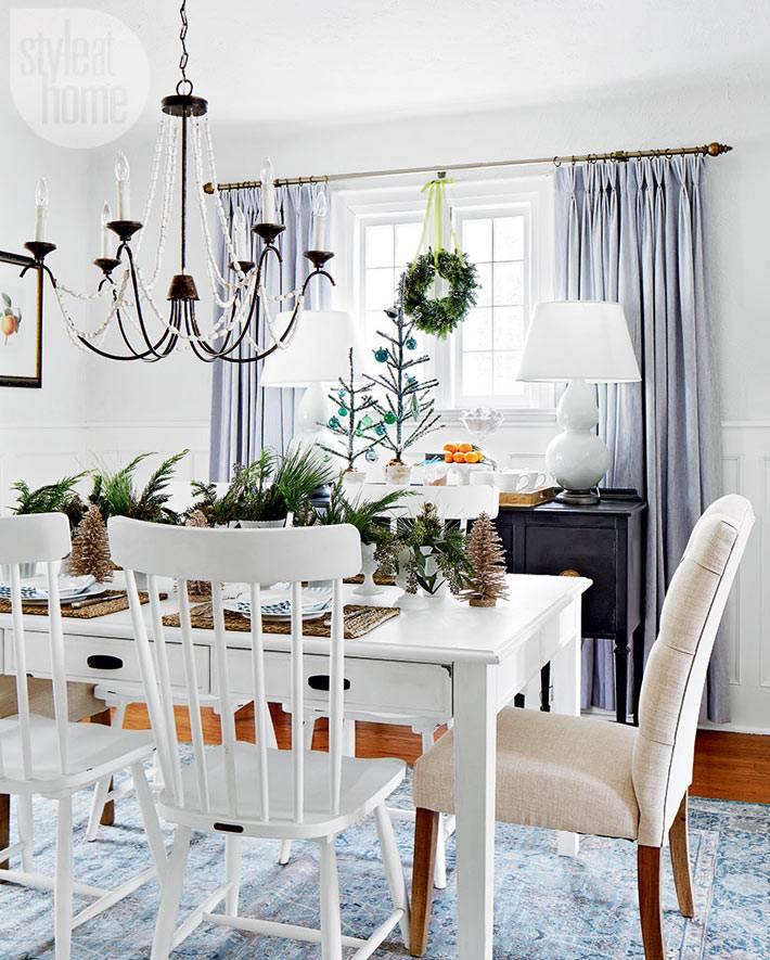 рождественское украшение столовой комнаты с елками и мандаринами