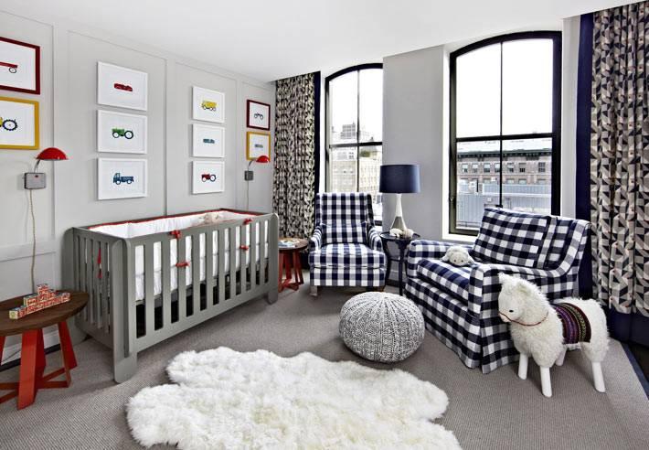 кресла в сине-белую клетку и серая детская кроватка в комнате