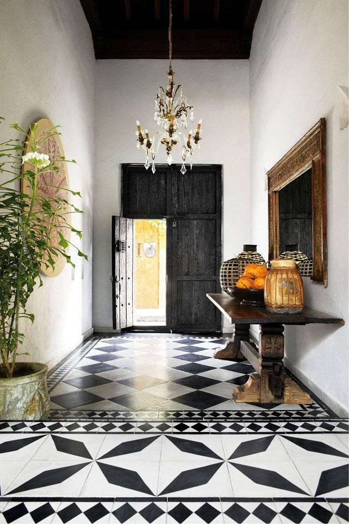 массивная входная дверь черного цвета и черно-белый кафельный пол