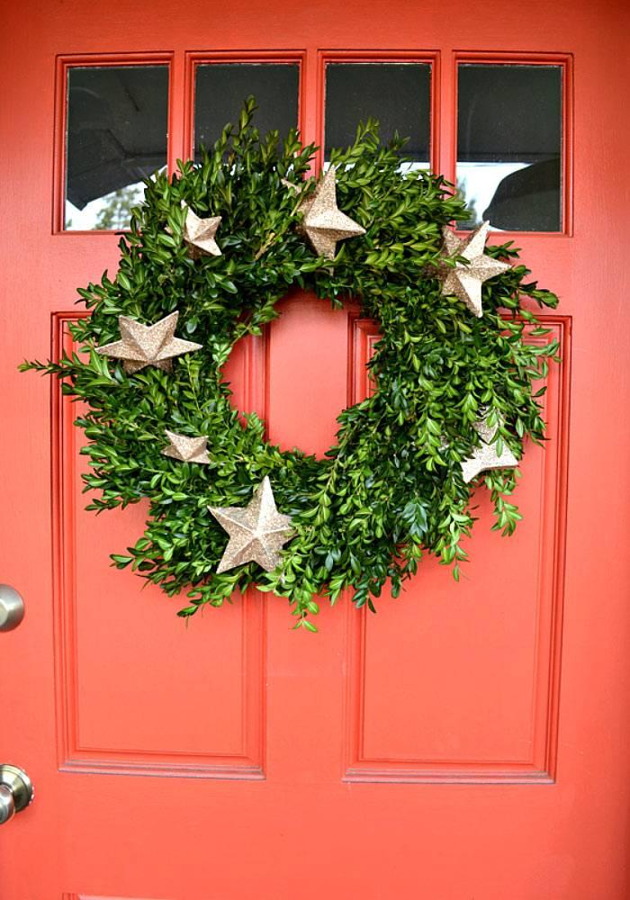 рождественский венок из зелени на красной двери в доме