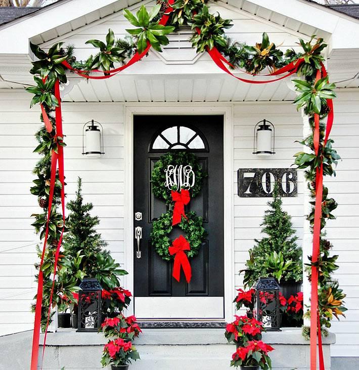 зелень и красные ленты украшают крыльцо дома