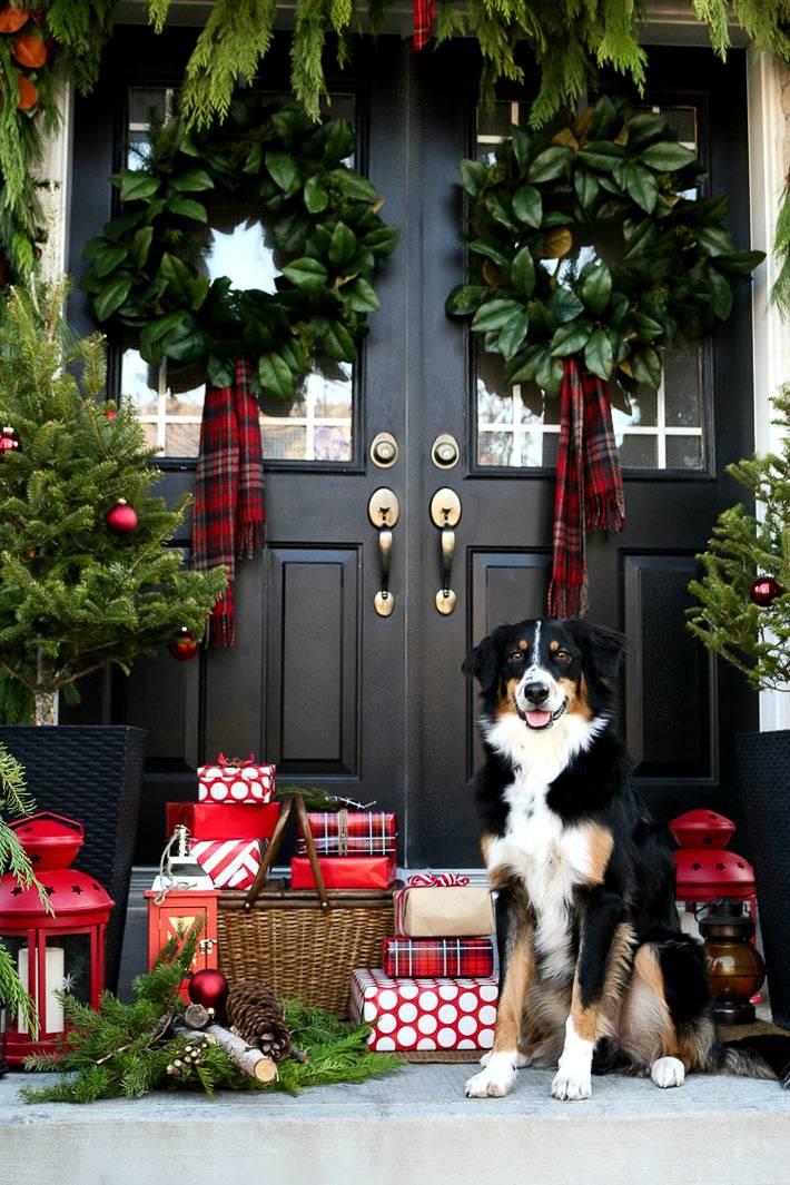 черная входная дверь с новогодними украшениями - еловыми венками и гирляндами