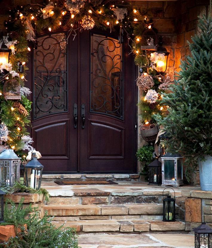 красивый частный дом, украшенный к новогодним праздникам гирляндами