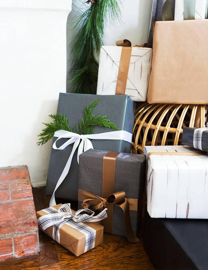 красиво упакованные подарки с лентами под ноговогодней ёлкой