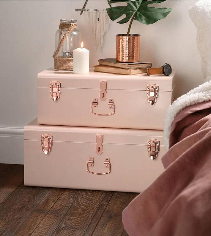 чемоданы возле кровати в спальне пыльно-розового цвета