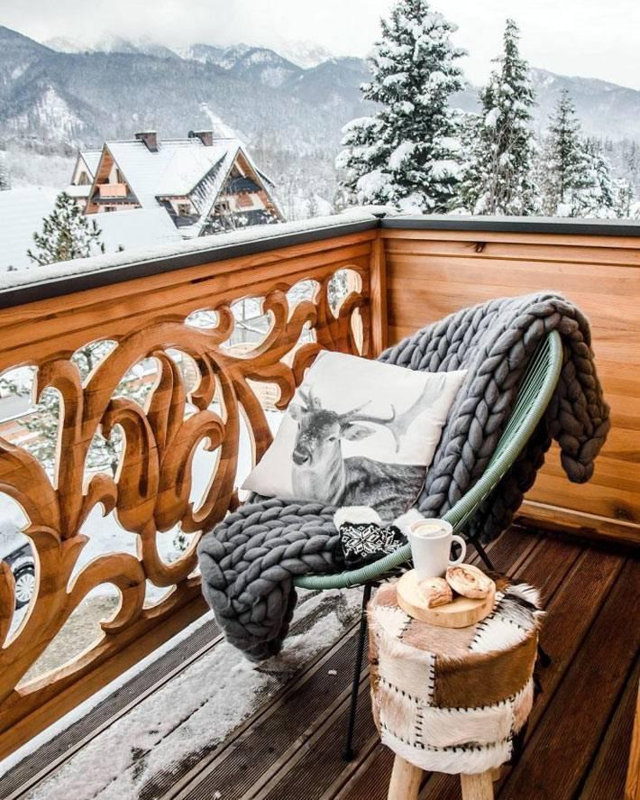 деревянный резной балкон с креслом и вязаным пледом
