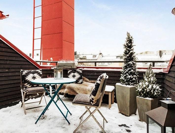 живые ёлки в кадках на открытом городском балконе в снегу