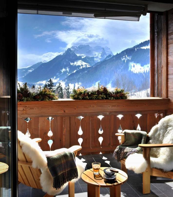 уютный зимний декор балкона с краслами и видом на заснеженные горы