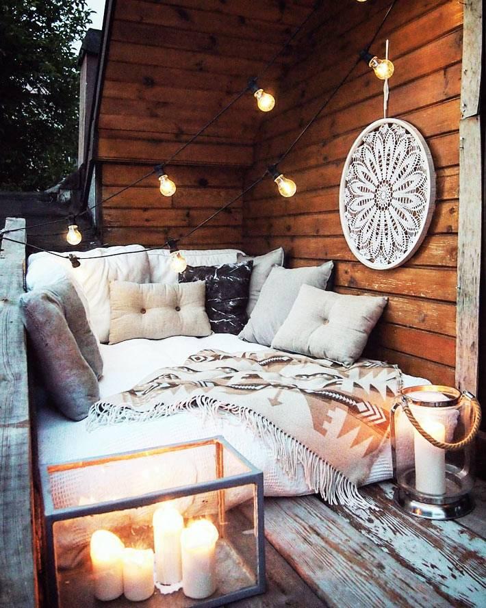 комфортный балкон с матрасом, подушками, гирляндами и ловцом снов