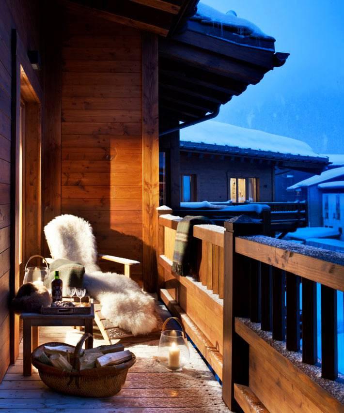 уютный пушистый плед на деревянном кресле на открытом балконе