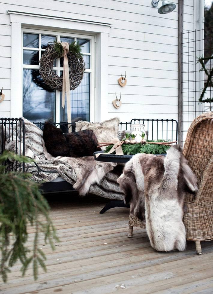 зимнее новогоднее украшение террасы с меховыми пледами