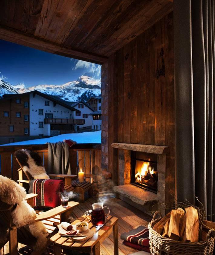 камин и свечи в уютной обстановке зимней террасы загородного дома