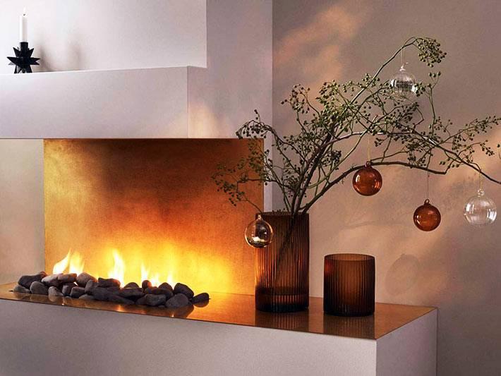 зеленая ветка в вазе украшена новогодними шарами разного цвета